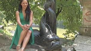 Extremely girl is sitting near the font in nice green dress